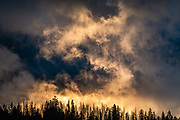 """Sunset dramatically backlights clouds at Green River Lakes Campground, in the Wind River Range, Bridger-Teton National Forest, Rocky Mountains, Wyoming, USA. The Continental Divide follows the crest of the """"Winds""""."""