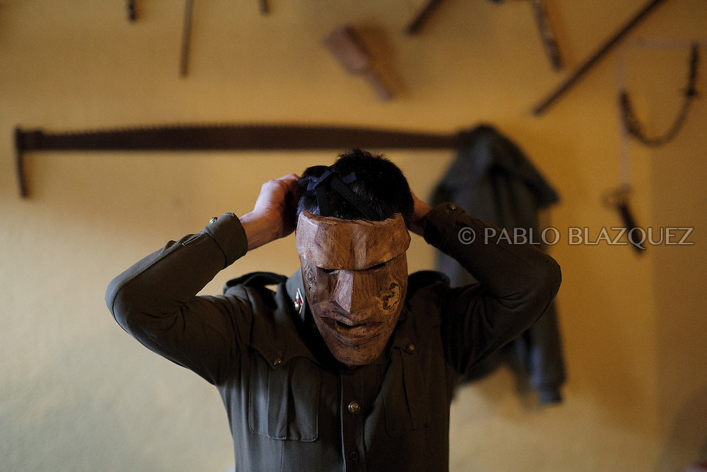 A Machurrero from Pedro Bernardo wears a mask before walking the streets during carnival on February 6, 2016 in Pedro Bernardo, in Avila province, Spain. The origins of this pagan festival are unknown. The Machurreros wear wood masks, a military dress, black handkerchief, cowbells, and hold wicker stick. The festival disappeared after Dictator Franco forbid carnival festivals in 1937, but it was recently recovered. Before disappearing, male villagers after the military service, used to dress as Machurreros as they run along the streets scaring children and adults with their wicker stick to bring fertility to the land and expel the evil spirits. (© Pablo Blazquez)