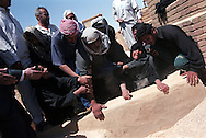 The family of Selman Khalaf bury his 12 year old son Ahmed Selman Khalef in the Shiite sacred burial ground after he was shot in a car with his father by US forces at a check point near Baghdad..Najaf, Iraq. 02 May 2003..Photo © J.B. Russell