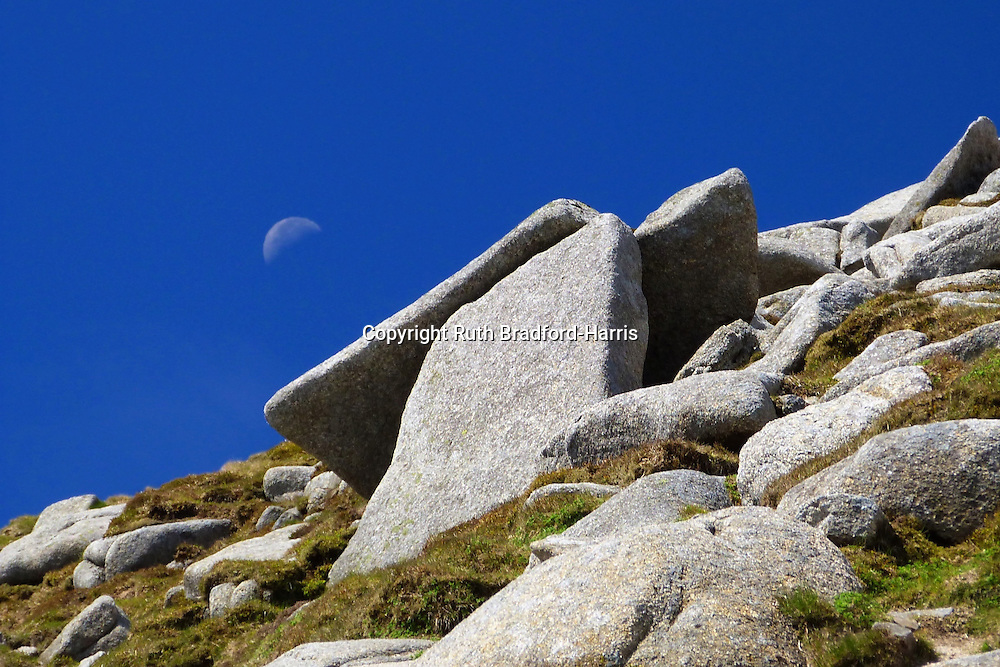 Ascending the rocks to the summit of Goat Fell, Isle of Arran, Scotland. A dolmen-like structure (a natural, glacially smoothed Granite outcrop) was reminiscent of Stonehenge, especially with the first quarter Moon in the deep blue sky above!<br />