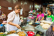 27 APRIL 2013 - BANGKOK, THAILAND:   A woman runs a street food stall in Talat Noi. The Talat Noi neighborhood in Bangkok started as a blacksmith's quarter. As cars and buses replaced horse and buggy, the blacksmiths became mechanics and now the area is lined with car mechanics' shops. It is one the last neighborhoods in Bangkok that still has some original shophouses and pre World War II architecture. It is also home to a  Teo Chew Chinese emigrant community.         PHOTO BY JACK KURTZ