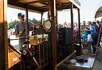 Brian Thompson disconnects the piping from his 1910 Lolly used to run a second steam engine to make ice cream that Kristie LeGates dishes out during the Steamboat Races at Lee's Mills in Moultonboro on Thursday afternoon.  (Karen Bobotas/for the Laconia Daily Sun)