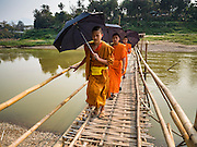 11 MARCH 2016 - LUANG PRABANG, LAOS:   Buddhist monks cross a bamboo foot bridge across the Nam Khan River near Luang Prabang. The bridge is seasonal. Villagers put it up every year, at the at the start of the dry season and take it down when the Nam Khan floods during the rainy season.  Laos is one of the poorest countries in Southeast Asia. Tourism and hydroelectric dams along the rivers that run through the country are driving the legal economy.     PHOTO BY JACK KURTZ