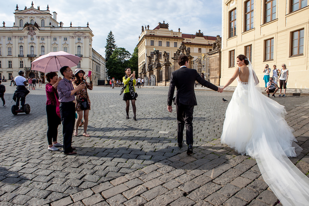"A ""just married"" couple - surrounded by tourists - is getting photographed close to the Prague Castle gate. Prague Castle was most likely founded in around 880 by Prince Bořivoj of the Premyslid Dynasty (Přemyslovci). According to the Guinness Book of World Records, Prague Castle is the largest coherent castle complex in the world, with an area of almost 70,000 m². A UNESCO World Heritage site, it consists of a large-scale composition of palaces and ecclesiastical buildings of various architectural styles, from the remains of Romanesque-style buildings from the 10th century through Gothic modifications of the 14th century."