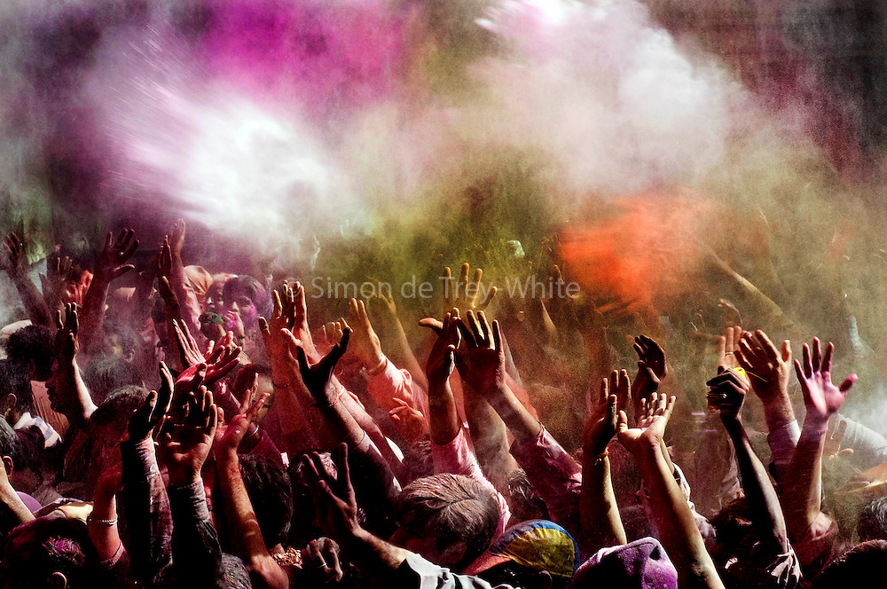 Hindu's celebrate Holi in the Banke Bihari Temple in Vrindavan, in the Mathura district of Uttar Pradesh, India , 1st March 2010. <br /> <br /> Holi, also called the Festival of Colours, is a spring festival celebrated by Hindus, Buddhists, Sikhs, Jains and others. It is primarily observed in India, Nepal, Srilanka, Pakistan, Bangladesh, and countries with large Indic diaspora populations, such as Suriname, Guyana, South Africa, Trinidad, UK, USA, Mauritius, and Fiji. In West Bengal of India and Bangladesh it is known as Dolyatra (Doul Jatra) or Basanta-Utsav (&quot;spring festival&quot;). The most celebrated Holi is that of the Braj region, in locations connected to the god Krishna: Mathura, Vrindavan, Nandagaon, and Barsana. These places have become tourist destinations during the festive season of Holi, which lasts here to up to sixteen days.<br /> The main day, Holi, also known as Dhulheti, Dhulandi or Dhulendi, is celebrated by people throwing colored powder and colored water at each other. Bonfires are lit the day before, also known as Holika Dahan (burning of Holika) or Chhoti Holi (little Holi). The bonfires are lit in memory of the miraculous escape that young Prahlad accomplished when Demoness Holika, sister of Hiranyakashipu, carried him into the fire. Holika was burnt but Prahlad, a staunch devotee of god Vishnu, escaped without any injuries due to his unshakable devotion. Holika Dahan is referred to as Kama Dahanam in Andhra Pradesh.<br /> <br /> PHOTOGRAPH BY AND COPYRIGHT OF SIMON DE TREY-WHITE<br /> <br /> + 91 98103 99809<br /> + 91 11 435 06980<br /> +44 07966 405896<br /> +44 1963 220 745<br /> email: simon@simondetreywhite.com photographer in delhi
