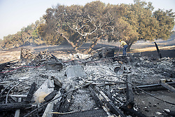 October 29, 2019, Windsor, California: Santa Barbara County Firefighter Shankar Tillotson, mops up a hot spot of a barn that burned Sunday. (Credit Image: © Erick Madrid/ZUMA Wire)