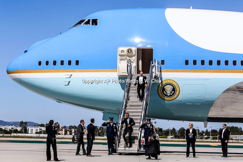President Barack Obama salutes as he disembarks from Air Force One upon his arrival at Los Angeles International Airport in Los Angeles on Saturday, Oct. 10, 2015.