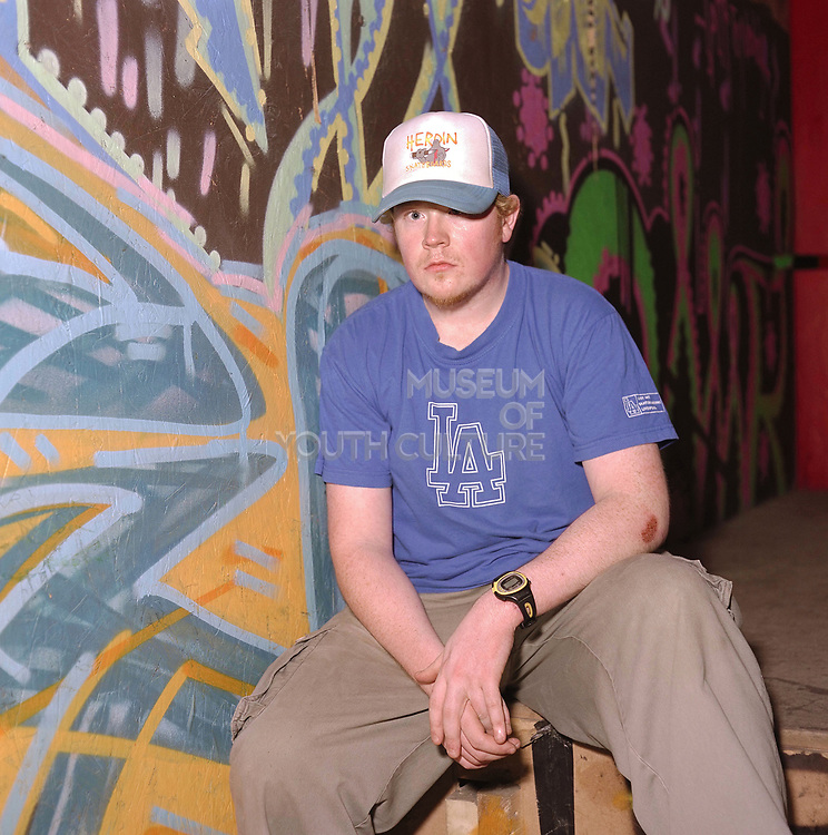A young teenage boy sat in front of graffiti, Cardiff, UK, 2000's
