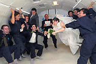 Bride Erin Finnegan, right, of New York, NY, and bridegroom Noah Fulmor are helped by the rest of the wedding party as Zero Gravity Corporation co-founder Richard Garriott, center, officiates during the first weightless wedding aboard a specially-equipped Boeing 727, while flying over the Gulf of Mexico after taking off from Titusville, Florida, June 20, 2009. REUTERS/Phelan M. Ebenhack (UNITED STATES)