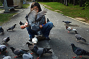 A young girl feeds pigeons in Nong Buak Hard Public Park in Chiang Mai Thailand.