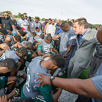 Life Remodeled CEO Chris Lambert, second right, leads Detroit's Cody High School's Varsity football team in prayer after practice the day before the first game on the school's new field.