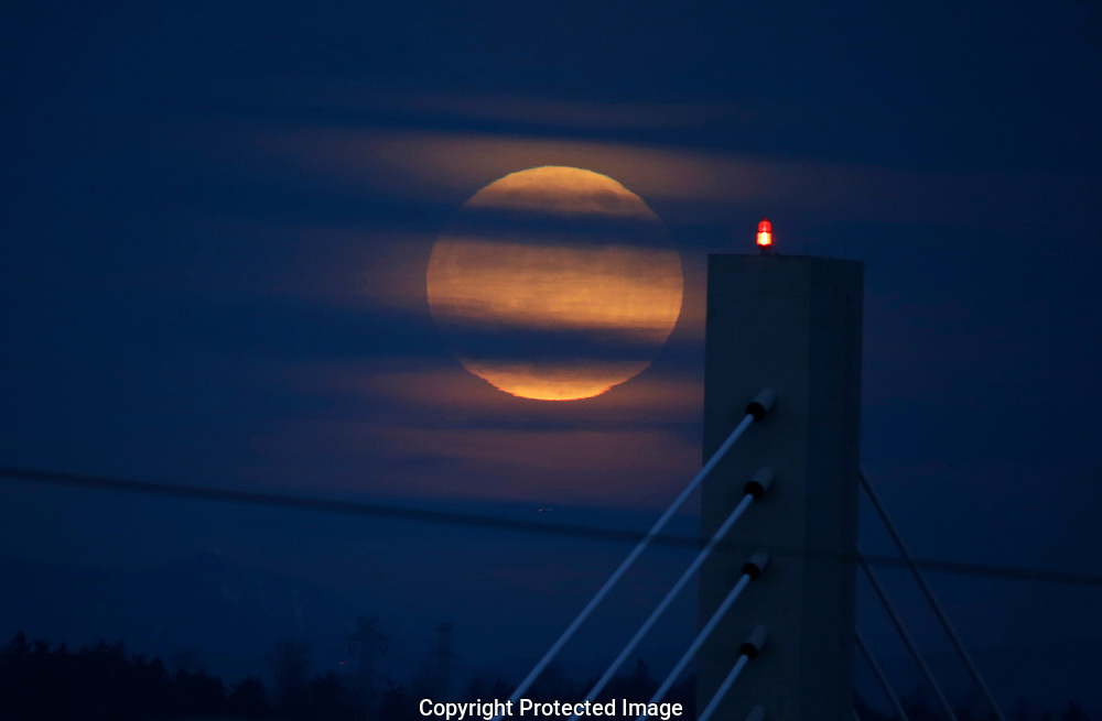 Full moon also known as supermoon due to the proximity to the earth, rises near the 21st St. Bridge in Tacoma Wash. on Monday, Jan. 1, 2018. (Photo/John Froschauer)
