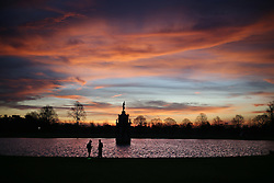 © Licensed to London News Pictures. 28/12/2015. London, UK.  A cyclist takes photographs of a friend as the sun rises over the Diana Fountain in Bushy Park. Photo credit: Peter Macdiarmid/LNP