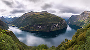 Geirangerfjord is a fjord in the Norwegian county Møre og Romsdal. It is a 15 km long arm of Storfjorden. The village Geiranger is located at the end of the fjord. The picture is captured from the viewpoint Ørnesvingen, with views to the Seven Sisters waterfalls, and the mountain farm Knivsflå. Stitched panorama | Geirangerfjorden er en fjord på Sunnmøre i Møre og Romsdal. Den er 15 kilometer lang og utgjør en arm av Storfjorden. Innerst i fjorden ligger Geiranger. Her med utsikt fra Ørnesvingen med utsikt til fossene de Syv Søstre og fjellgården Knivsflå. Sammensett panorama.