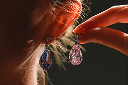 "© Licensed to London News Pictures. 10/04/2017. London, UK. A model presents ""The Apollo Blue"", a fancy blue vivid diamond weighing 14.54 carats (Est. USD 38-50m) and ""The Artemis Pink"", a fancy intense pink diamond weighing 16.00 carats (Est. USD 12.5-18m).   The diamonds are the most valuable earrings ever to appear at auction and will be offered for sale by Sotheby's on 16 May in Geneva. Photo credit : Stephen Chung/LNP"
