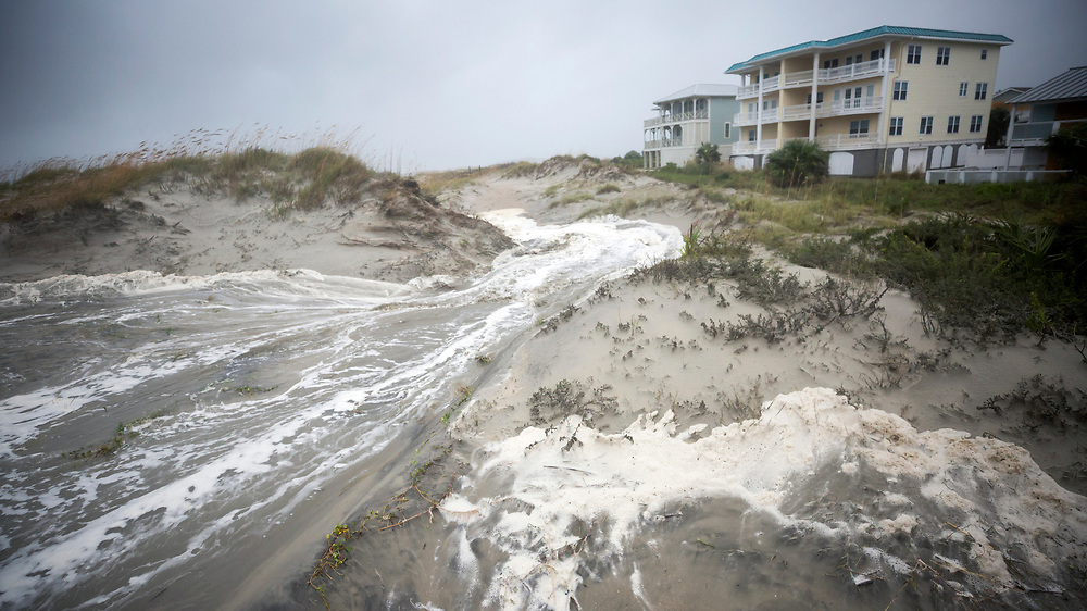 Waves from Tropical Depression Irma wash into the sand dunes that separate the homes from the beach, Monday, Sept., 11, 2017 on Tybee Island, Ga. (AP Photo/Stephen B. Morton)