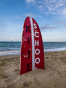 Half a surfboard buried in the sand advertises for a kite school on the beach in Cabarete, Dominican Republic.