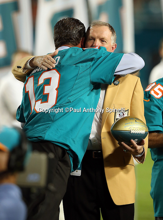 Former Miami Dolphins quarterback Dan Marino (13) hugs former Miami Dolphins quarterback Bob Griese during a halftime ceremony honoring the 50 all-time Dolphin great players during the Miami Dolphins NFL week 14 regular season football game against the New York Giants on Monday, Dec. 14, 2015 in Miami Gardens, Fla. The Giants won the game 31-24. (©Paul Anthony Spinelli)