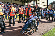A young disabled Bolton Wanderers fan is helped to safety after the pitch invasion during the EFL Sky Bet League 1 match between Port Vale and Bolton Wanderers at Vale Park, Burslem, England on 22 April 2017. Photo by Mark P Doherty.