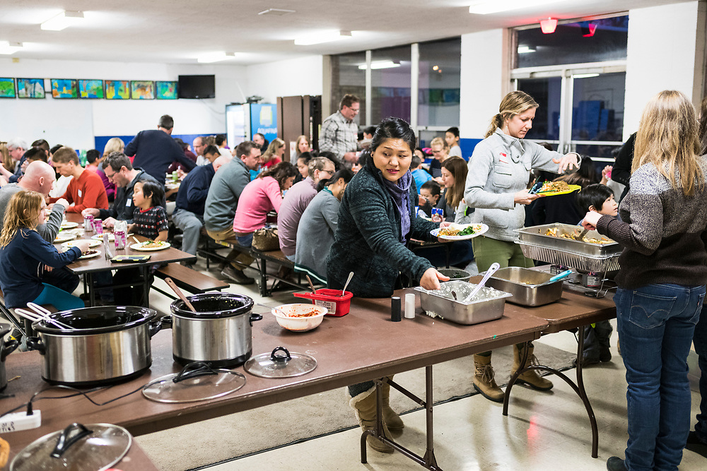 Families enjoy dinner during a lunar new year event hosted by Families Through Korean Adoption (FTKA) in the gym and school cafeteria of St. Dennis Church in Madison, Wis., on Feb. 10, 2018. The event celebrated the passing of the lunar new year, and is one of several events for FTKA-member families and children to gather and enjoy cultural fun, food and play. (Photo by Jeff Miller - www.jeffmillerphotography.com)