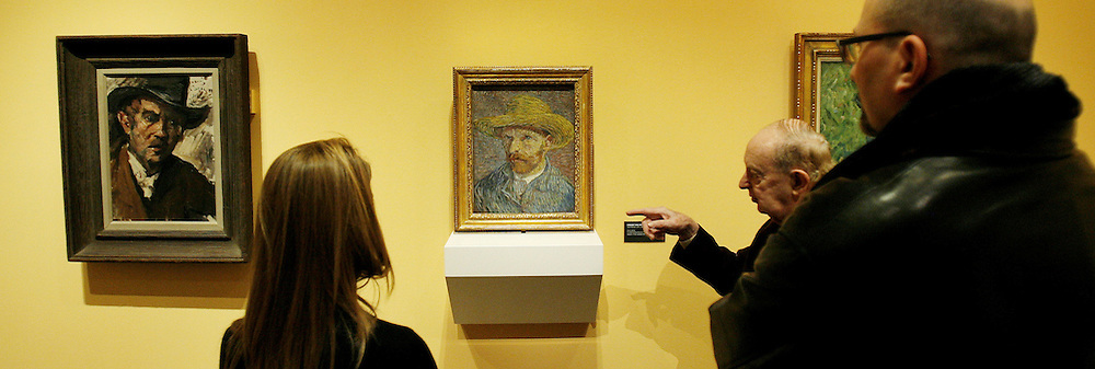 Three people look over Lovis Corinth's 'Self Portrait with Black Hat' (L) and Vincent van Gogh's 'Self Portrait with a Straw Hat' (R) at an exhibit exploring the influence of van Gogh on German and Austrian Expressionism at the Neue Galerie in New York, New York on Wednesday 21 March 2007. The exhibit, which features over 80 major paintings, will be open until 02 July 2007.