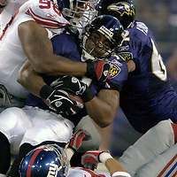 11 August 2006:  The Baltimore Ravens Jamal Lewis (C) rushes for 13 yards in the first quarter before being brought down by the New York Giants Fred Robbins (98) in a pre-season game won by the Giants 17-16 at M&T Bank Stadium in Baltimore, Md. .