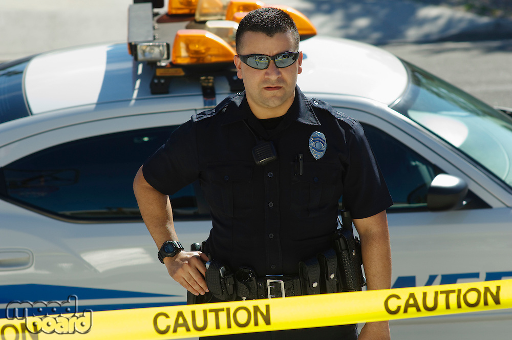 Police Officer Standing Behind Police Tape