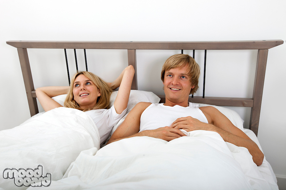 Thoughtful couple lying in bed at home