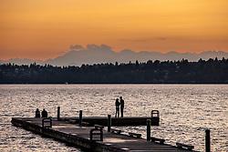 North America, United States, Washington, Kirkland, couple on dock on Lake Washington at sunset.