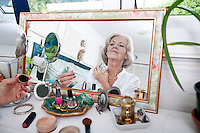 Mirror reflection of senior woman spraying perfume on herself at home