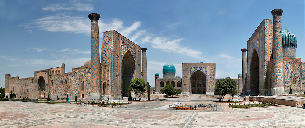 """Panoramic view of Registan Square, showing the Sher-Dor, 1619-36, (right), Tillya-Kori, 1646-60, (centre) and Ulugh Beg, 1417-20, (left) Madrasahs, Samarkand, Uzbekistan, pictured on July 15, 2010, in the morning. The Tillyah-Kori (gilded) Madrasah is part of the Registan Ensemble, surrounding a magnificent square. Commissioned by Yalangtush Bakhadur it is not only a school but also the grand mosque. The Sher-Dor Madrasah, commissioned by Yalangtush Bakhodur as part of the Registan ensemble, and designed by Abdujabor, takes its name, """"Having Tigers"""", from the double mosaic (restored in the 20th century) on the tympans of the portal arch showing suns and tigers attacking deer. The lancet arched portal of the Ulugh Beg Madradsah, commissioned by the scholarly Ulugh Beg, faces the square and high well-proportioned minarets flank the corners. It was restored in the early twentieth century. Samarkand, a city on the Silk Road, founded as Afrosiab in the 7th century BC, is a meeting point for the world's cultures. Its most important development was in the Timurid period, 14th to 15th centuries. Picture by Manuel Cohen."""