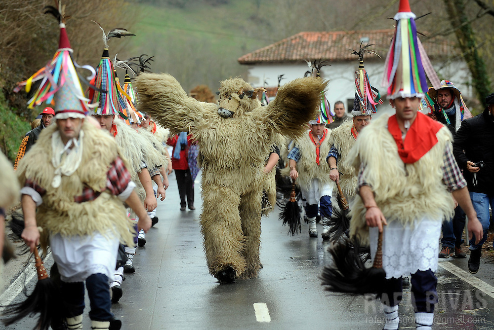 "A group of ""Joaldunak"" (""those who play the bell"") and a man dressed as Hartza (bear) (C) march carrying big cowbells tied to their backs as they take part in the ancient carnival of Ituren, in the northern Spanish province of Navarra, on January 28, 2014.   PHOTO/ RAFA RIVAS"