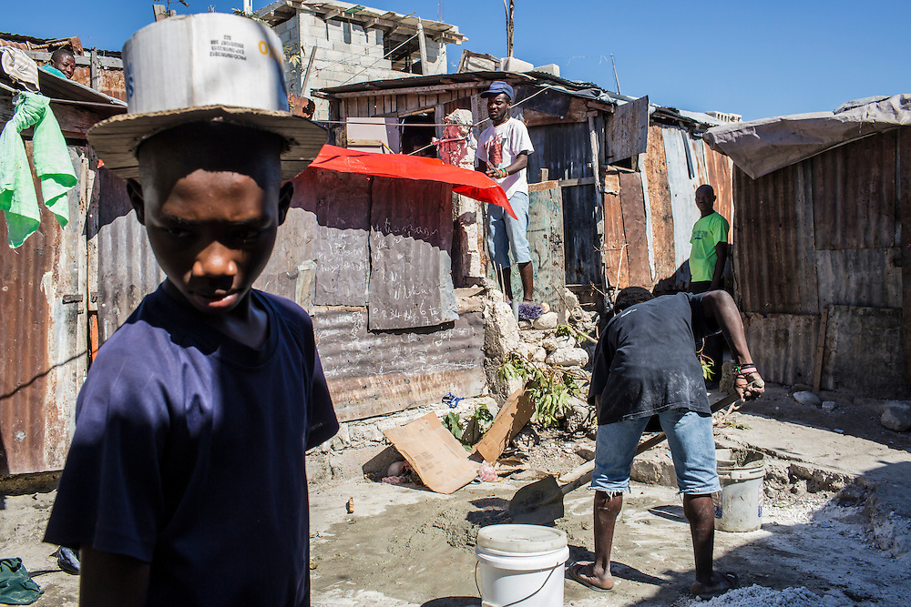 A boy wears a top hat he made himself out of cardboard as local residents work on repairing their houses on Thursday, December 18, 2014 in Port-au-Prince, Haiti. Fort National was among the hardest hit areas of Port-au-Prince in the 2010 earthquake, but rebuilding has been slow to non-existent. Residents still mostly lack electricity and running water.