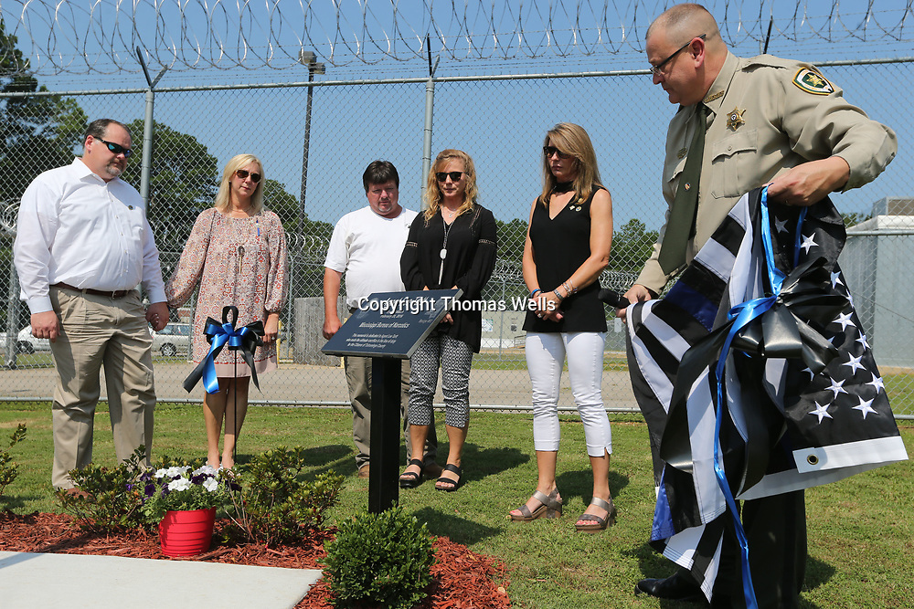 The family of MBN officer Lee Tartt watches as Tishomingo County Sheriff John Daugherty unviels a marker dedicated to Tartt who was killed during a 2016 standoff.