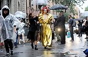 Models are escorted under umbrellas to the start of the Rodarte fashion show during New York Fashion Week, Sunday, Sept. 9, 2018. (AP Photo/Diane Bondareff)