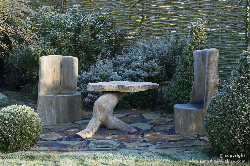 Rustic table and chairs on patio area paved with slate in winter. Woven willow screen behind. Design: John Massey, Ashwood Nurseries
