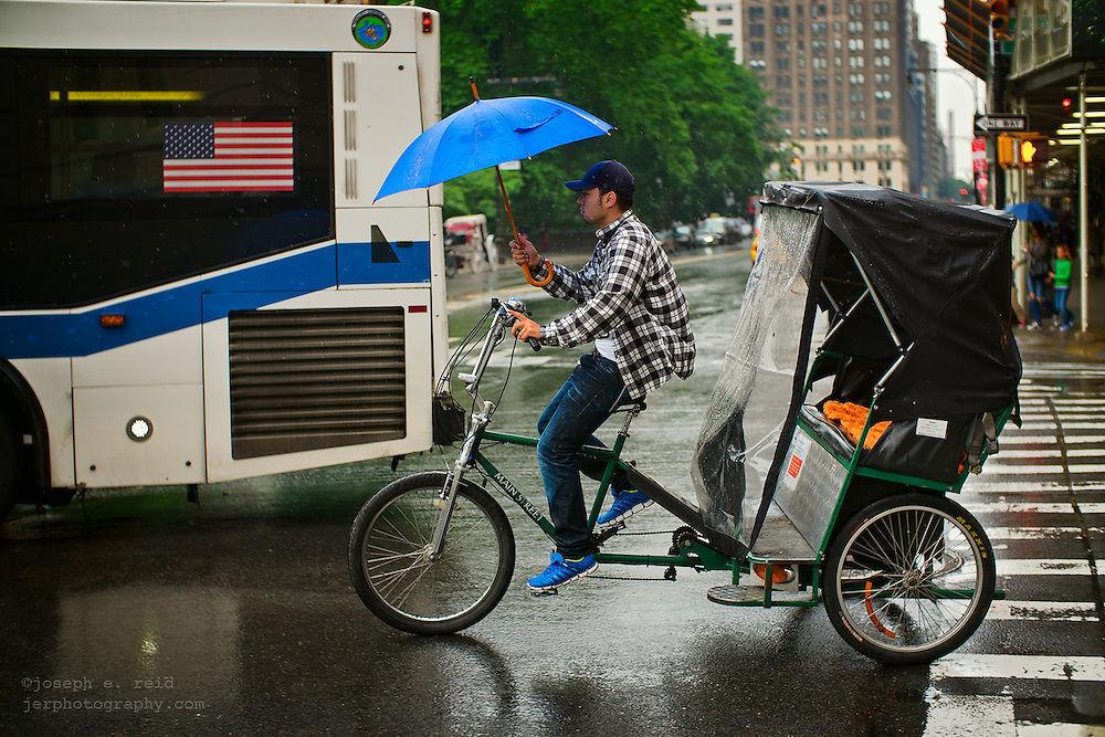 Man with blue umbrella driving pedicab near bus