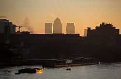 © Licensed to London News Pictures. 16/02/2016. London, UK. The top of buildings at Canary Wharf seen at Sunrise in central London on a cold winter morning. Temperatures in the capital dropped below zero last night. Photo credit: Ben Cawthra/LNP
