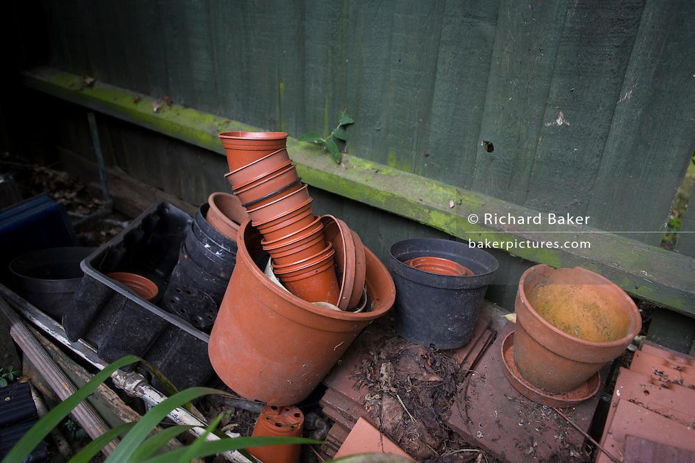 Flowerpots stored by fencing in the corner of an English back garden
