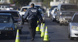 A policeman walks past vehicles whose owners would hand in their guns in Los Angeles, the U.S. Los Angeles police reclaimed guns here on Wednesday in response to the Dec. 14 school massacre in Newtown, Connecticut. Locals who handed in their guns could get cash coupon in return, December 26, 2012. Photo by Imago / i-Images...UK ONLY