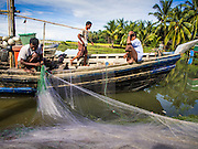 06 NOVEMBER 2014 - SITTWE, RAKHINE, MYANMAR: Rohingya Muslim fishermen repair their nets before leaving the pier in a Rohingya IDP camp near Sittwe. After sectarian violence devastated Rohingya communities and left hundreds of Rohingya dead in 2012, the government of Myanmar forced more than 140,000 Rohingya Muslims who used to live in and around Sittwe, Myanmar, into squalid Internal Displaced Persons camps. The government says the Rohingya are not Burmese citizens, that they are illegal immigrants from Bangladesh. The Bangladesh government says the Rohingya are Burmese and the Rohingya insist that they have lived in Burma for generations. The camps are about 20 minutes from Sittwe but the Rohingya who live in the camps are not allowed to leave without government permission. They are not allowed to work outside the camps, they are not allowed to go to Sittwe to use the hospital, go to school or do business. The camps have no electricity. Water is delivered through community wells. There are small schools funded by NOGs in the camps and a few private clinics but medical care is costly and not reliable.   PHOTO BY JACK KURTZ
