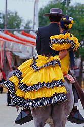 """Europe, Spain, Andalucia, Sevilla, man and woman in flamenco dress riding horse during """"Feria de Abril"""" festival, held annually in April"""