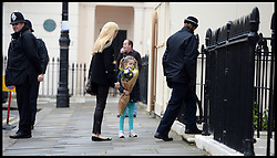 A young girl lays flowers outside the residence of Baroness Thatcher in Chester Square, London, UK, Tuesday 9 April, 2013, after her death on Monday April 8, 2013. Photo By Andrew Parsons / i-lmages.