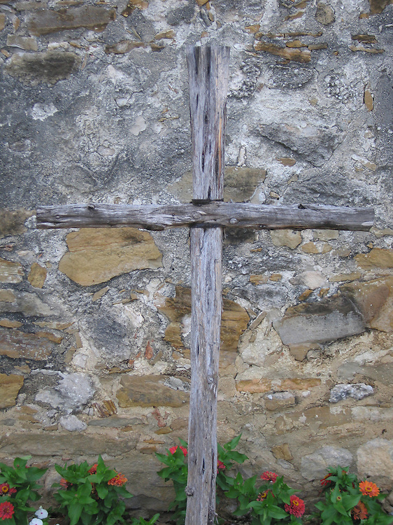 A cross in front of a wall