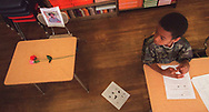 Kristopher Barden, age 8, of Detroit, sits next to Brianna Caddell's empty desk in her 3rd grade classroom at John C. Marshall Elementary School on Detroit's northwest side.  Another classmate Jamiel Silas, age 8, braught two silk roses to set on their former classmates desk.  Brianna's school books where still in the basket under her chair twenty days after her death.