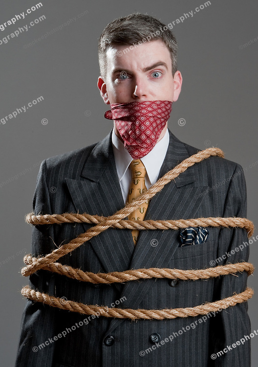 A well dressed man in a suit, tied with heavy rope and gagged with handkerchief.