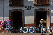 A cowboy walks past colorful memorial wreaths on sale for the Day of the Dead festival along a street in Santa Clara del Cobre, Michoacan, Mexico.