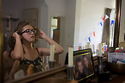 With bunting hanging, a 15 year-old teenager adjusts her hair before friends arrive at her home for her birthday party.