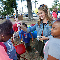 """Thomas Wells   Buy at PHOTOS.DJOURNAL.COM<br /> Joyner Elementary School teacher Lexie Wildmon uses colored hair spray to give a few students different colored hair at Friday's Joyner Fall Festival. The event which was hotsed by the Joyner PTA had the theme """"Joyner Town Fair""""."""