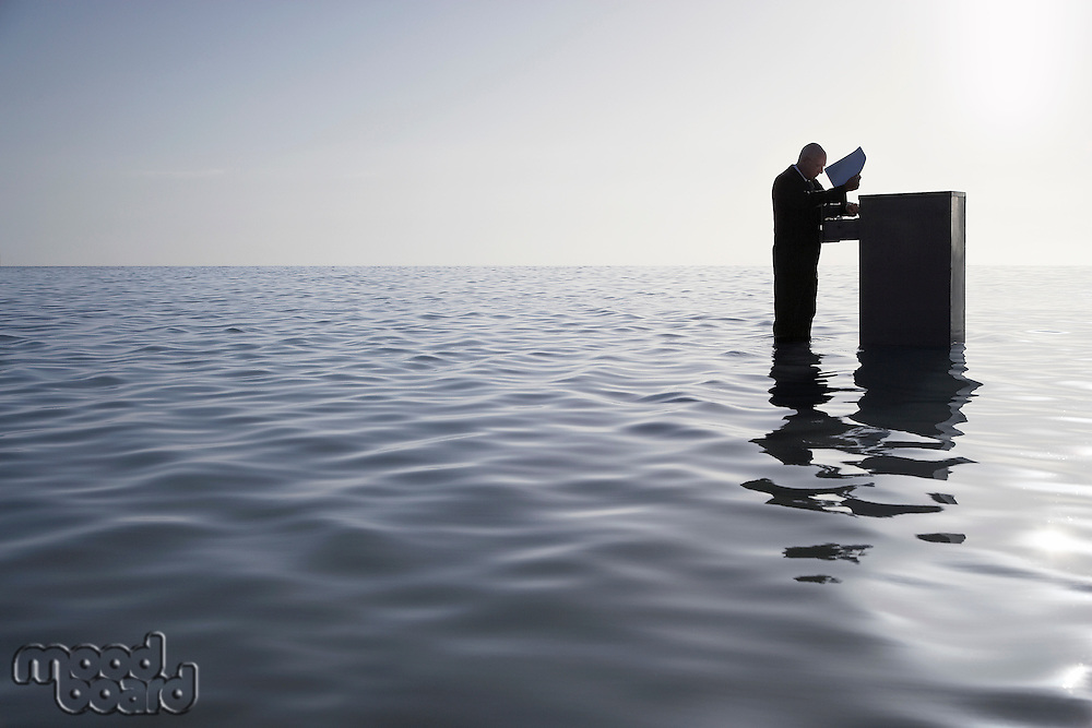 Silhouette of business man opening filing cabinet standing in sea side view